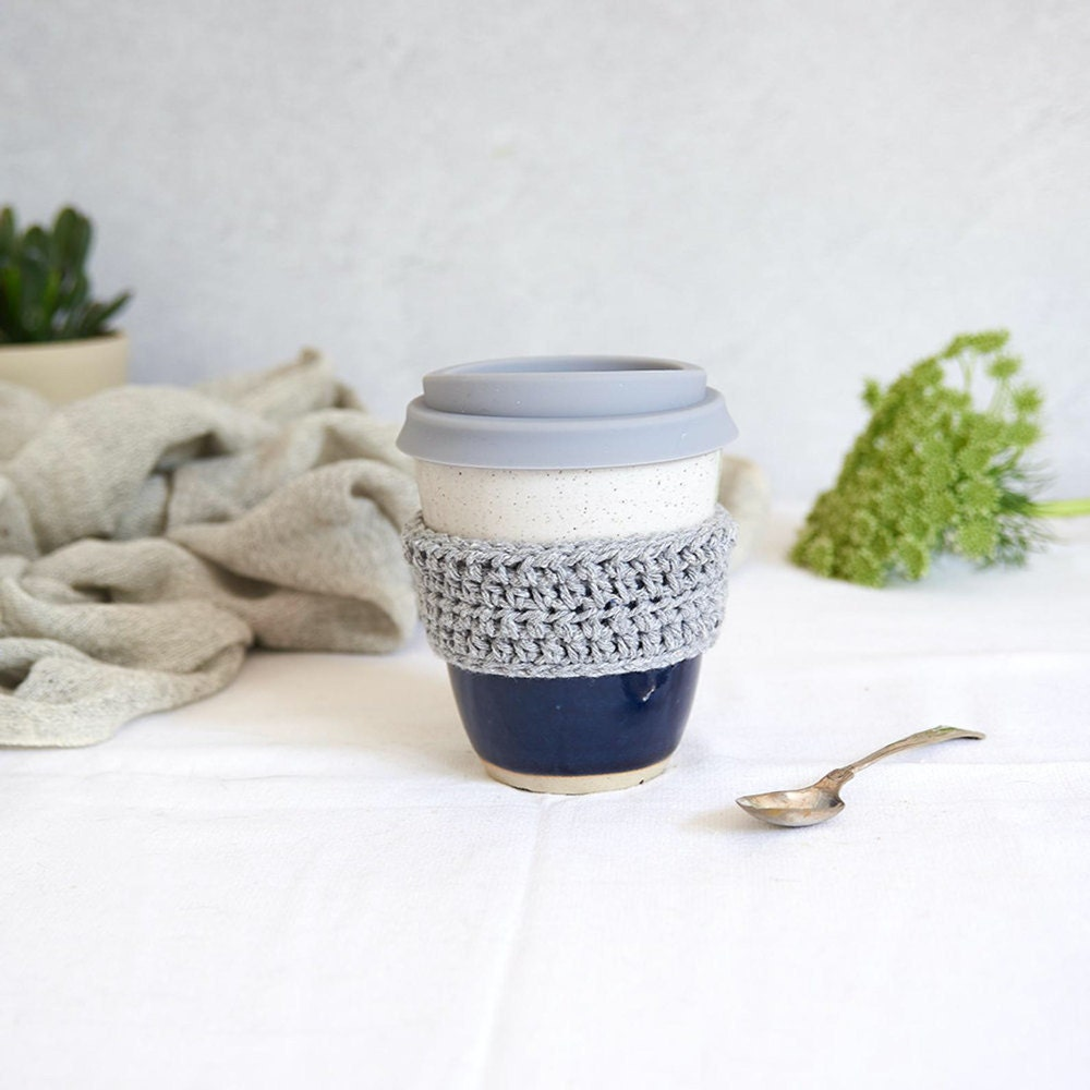 An eco-friendly ceramic travel mug with a crocheted grip from Libby Ballard Ceramics.