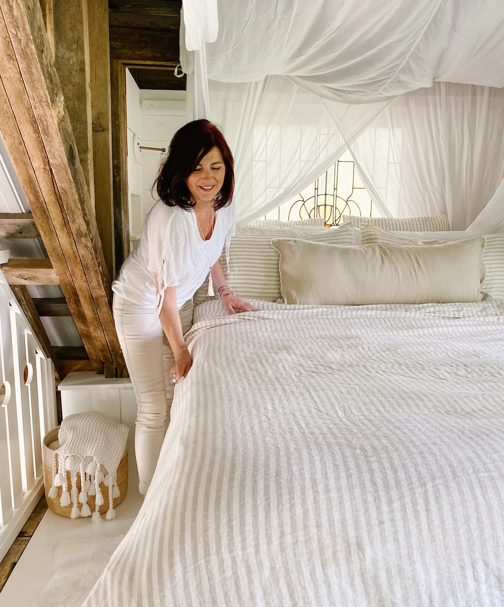 Lynne makes a bed with striped linen bedding and pom-pom pillowcases