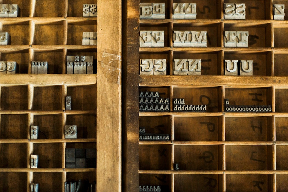A neatly organized shelf containing a variety of letter stamps in different sizes and styles.