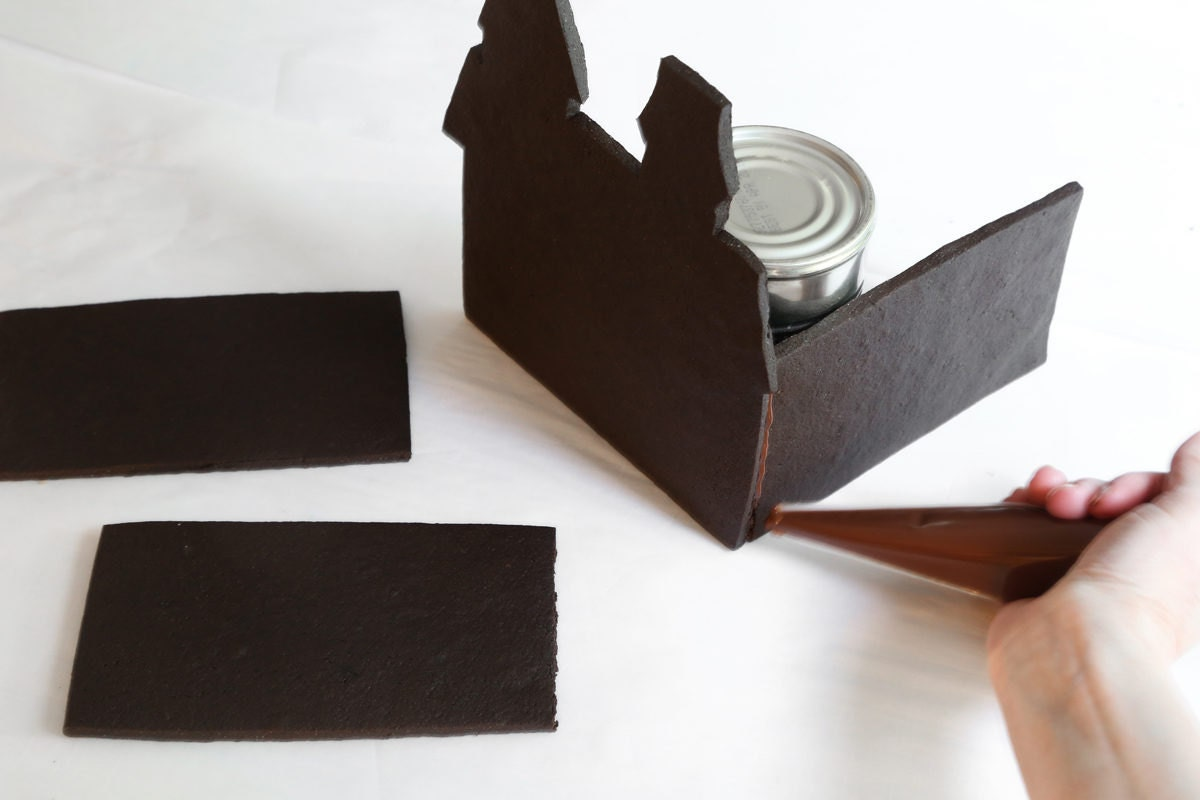 Assembling the castle using melted chocolate to bind the walls together.