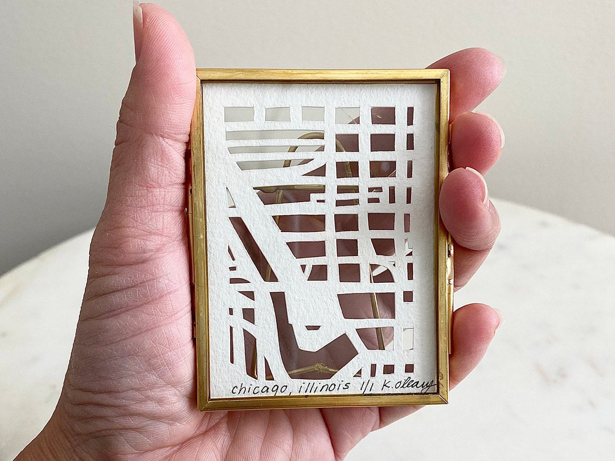 A model holds a miniature hand-cut map of Chicago, Illinois.