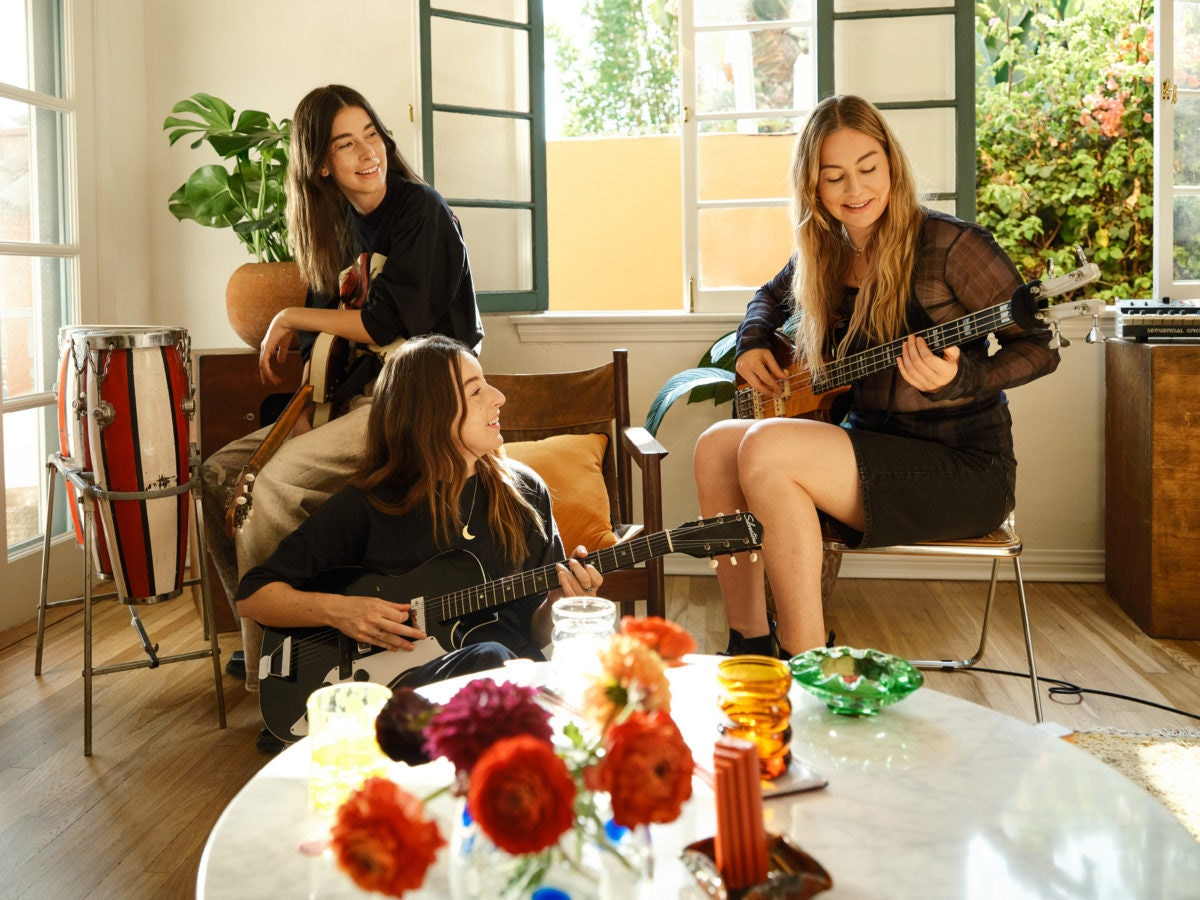 A photo of HAIM playing music in their home studio.