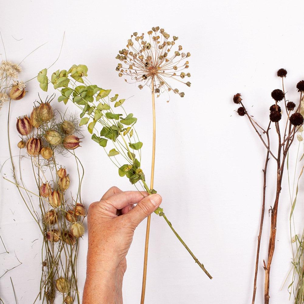 A person begins arranging their flower bouquet