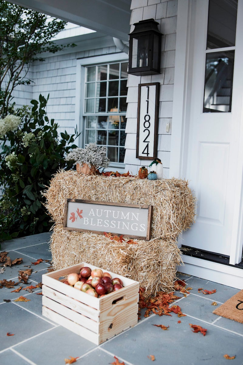 A rustic front porch styled with fall porch picks from Etsy.