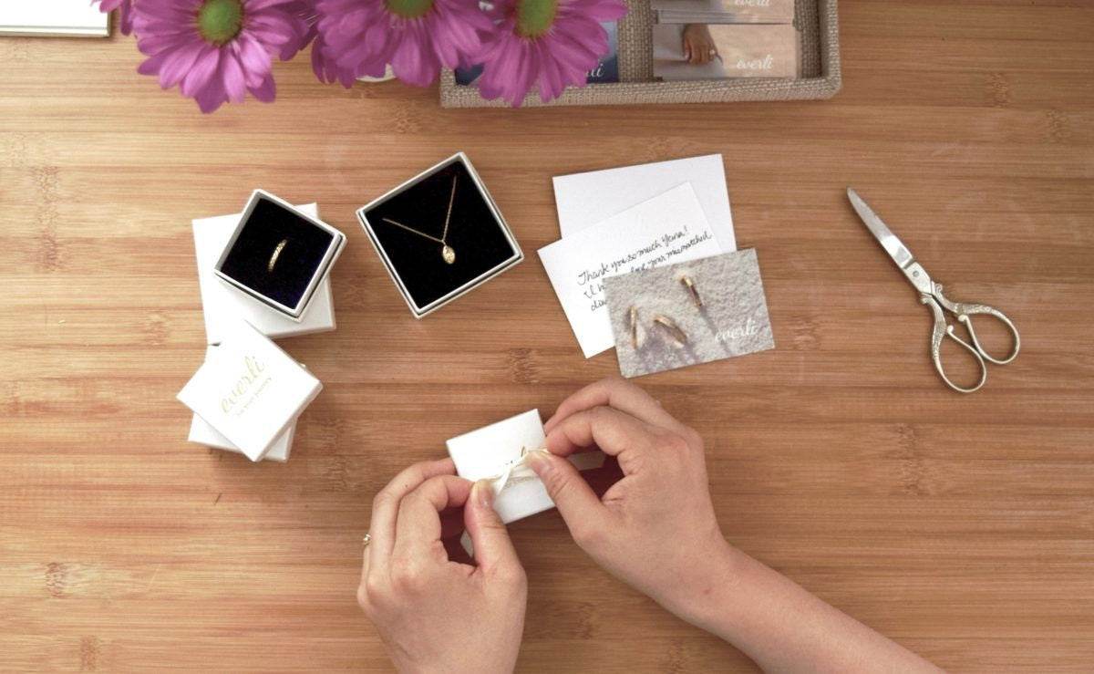 Shuang packaging jewelry orders at her desk