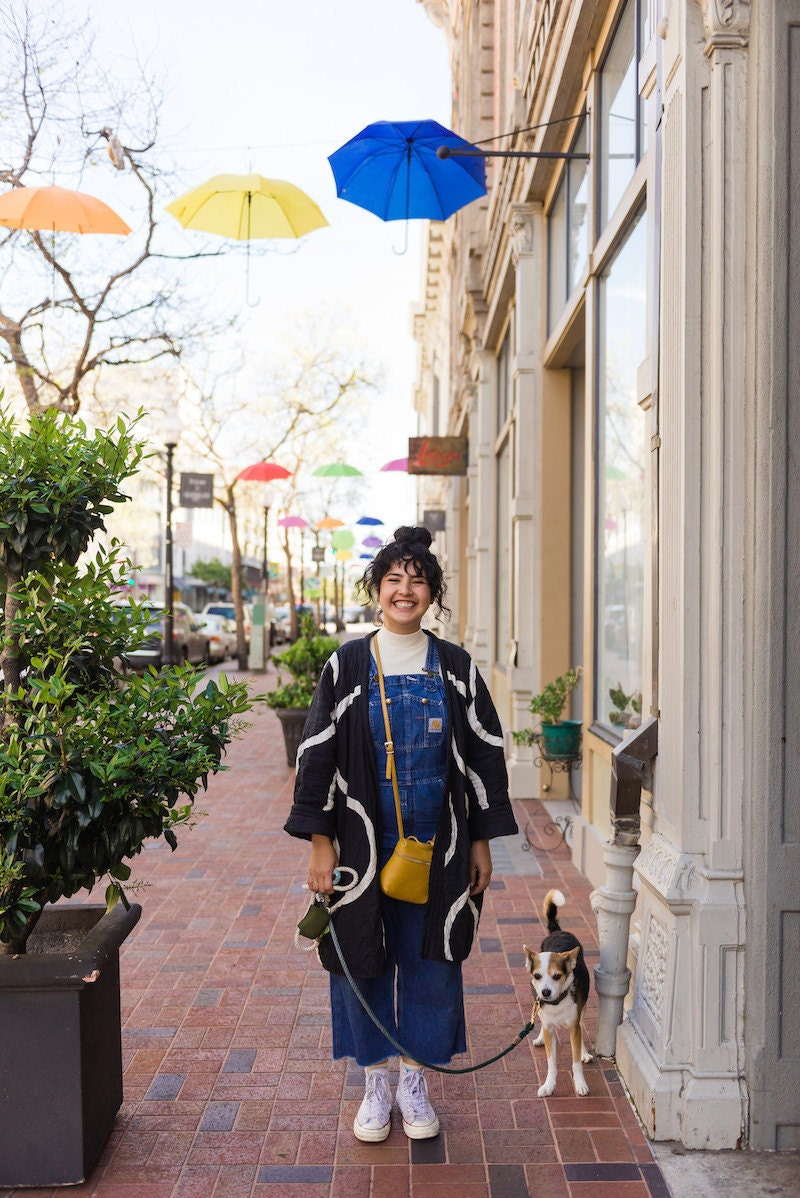 Melanie Abrantes stands and smiles on a colorful street in Oakland with her dog