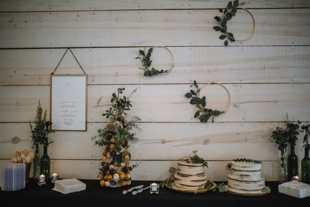 The dessert table, set with cakes and a donut stand, is accented by a trio of eucalyptus hoop wreaths on the wall behind it