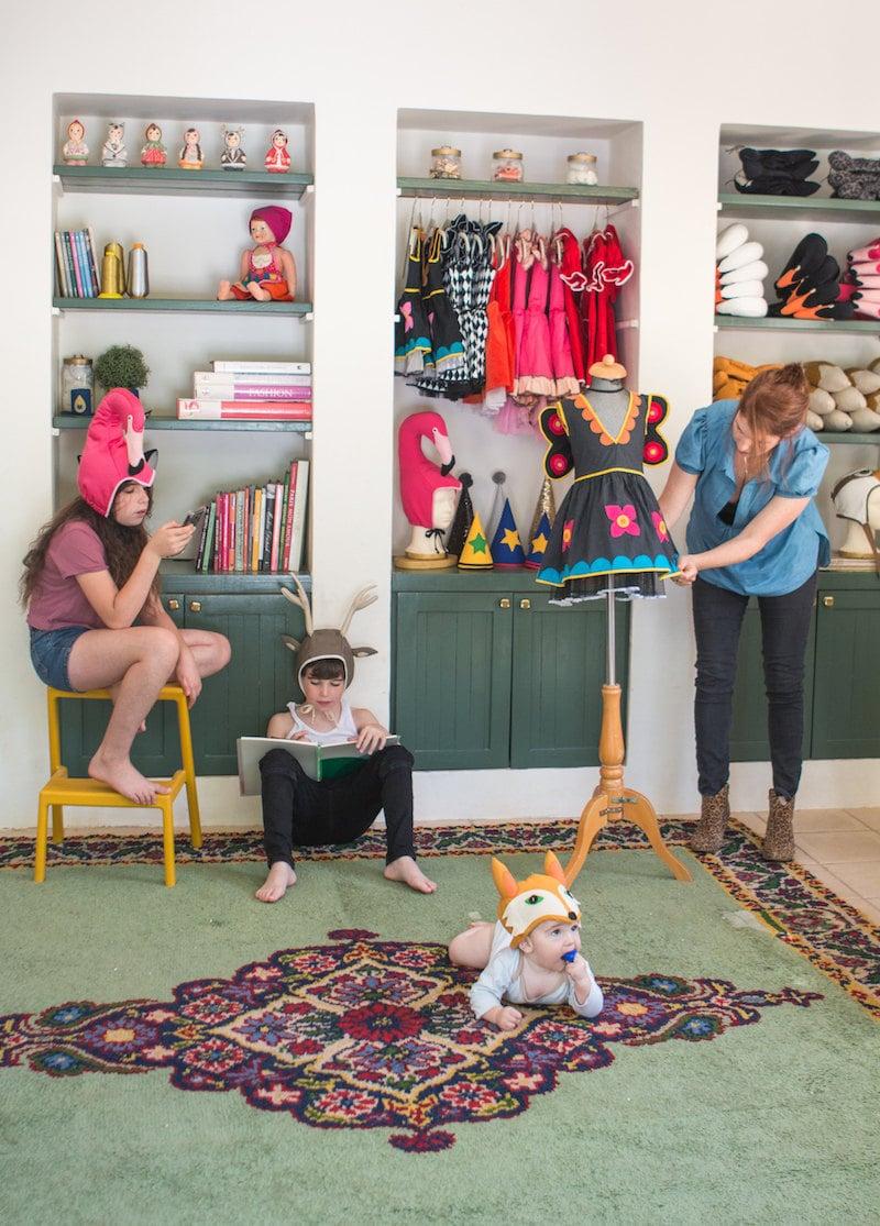 Inbal working in her studio alongside her three children