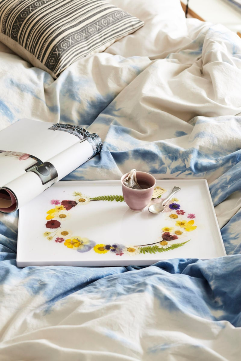 A styled photo of the completed DIY pressed flower tray laid out on a bed, carrying a cup of tea