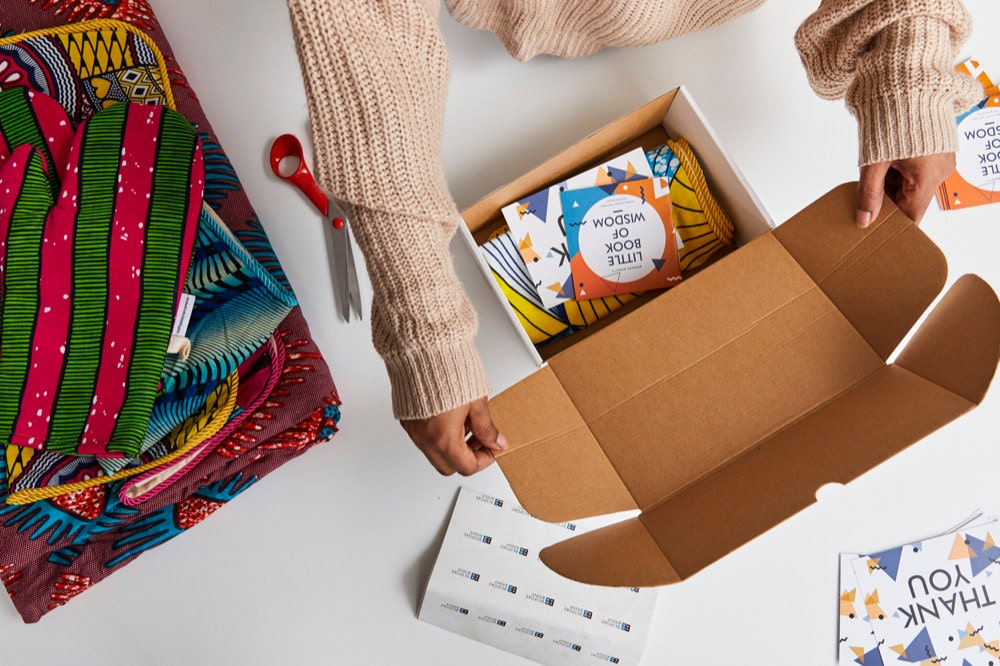 Natalie boxes an order, adding a free gift: a booklet of African proverbs.