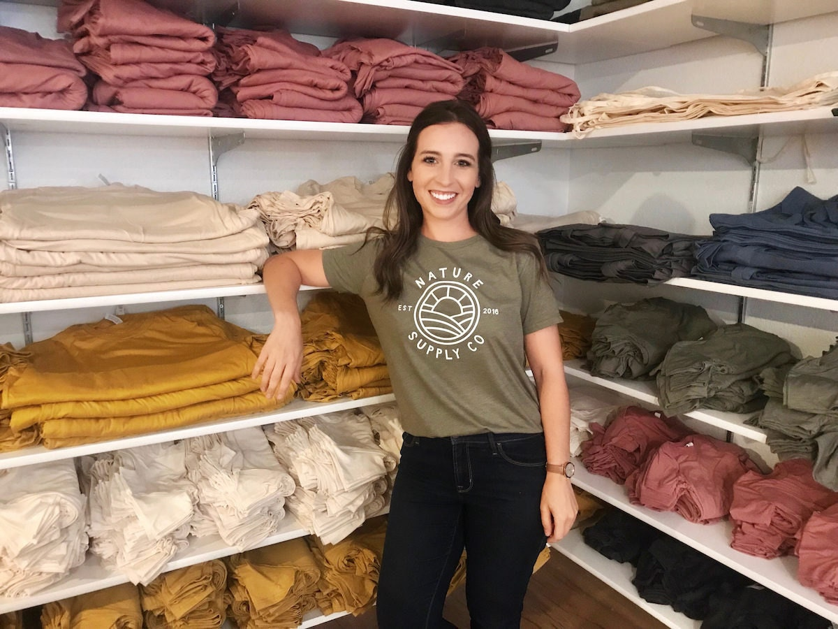 Lindsey poses with blank T-shirts and tote bags in her basement studio