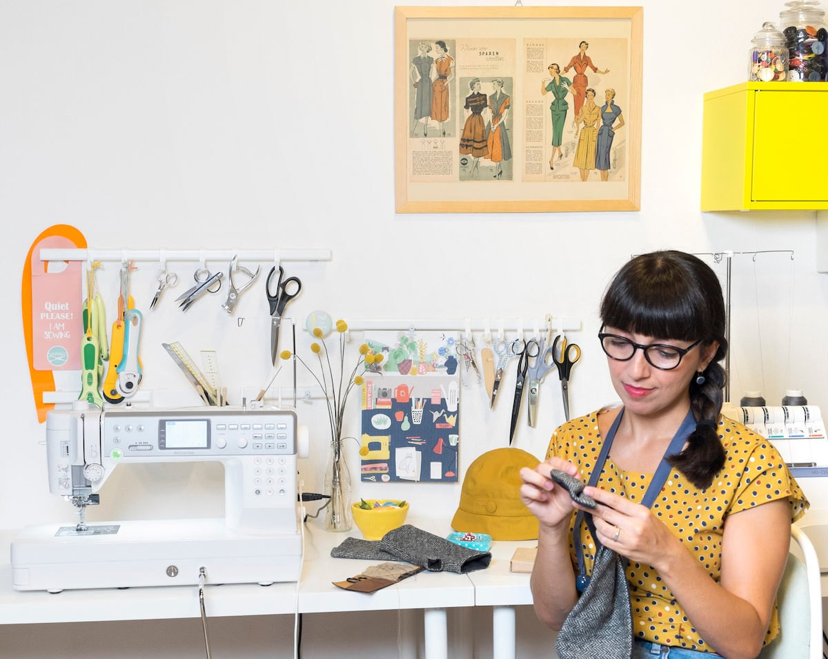 Simona sits at her desk and hand-stitches a piece