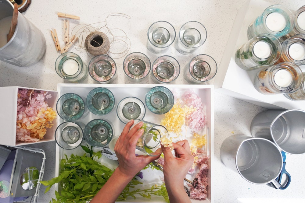 Rino arranges dried flowers in her decorative glass candle bases.