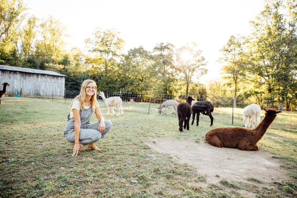 Kacie on the farm with several alpacas