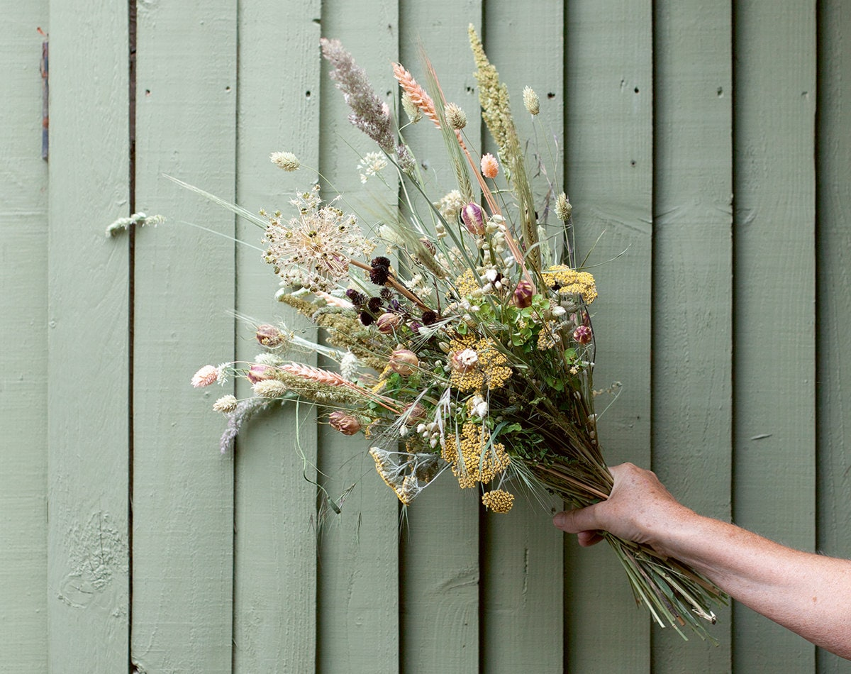 A bouquet of dried flowers held against a green wall.