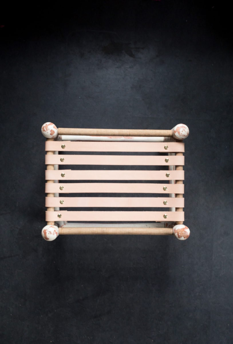 Vintage stool with leather straps attached to two parallel edges of the frame