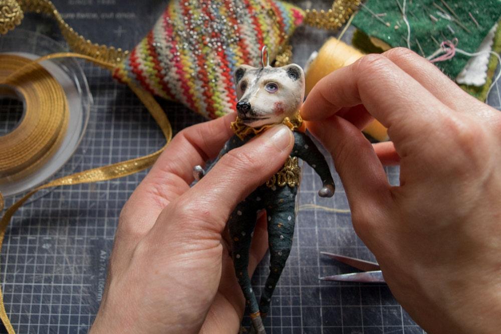 Kayleigh sews a ruffled collar onto her bear ornament
