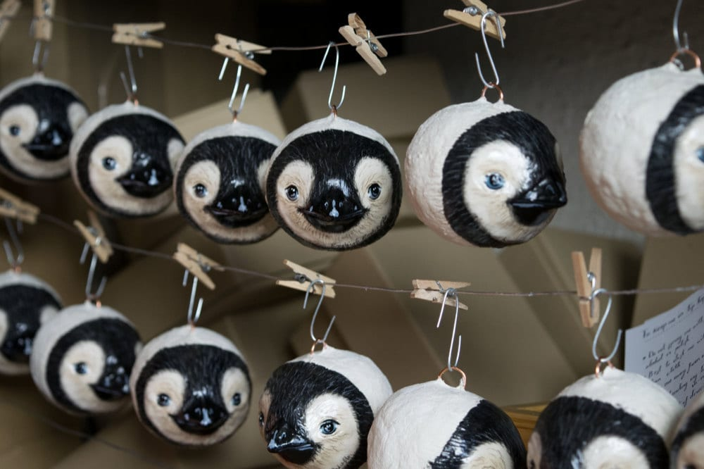 Painted baby penguin ornaments hanging up to dry