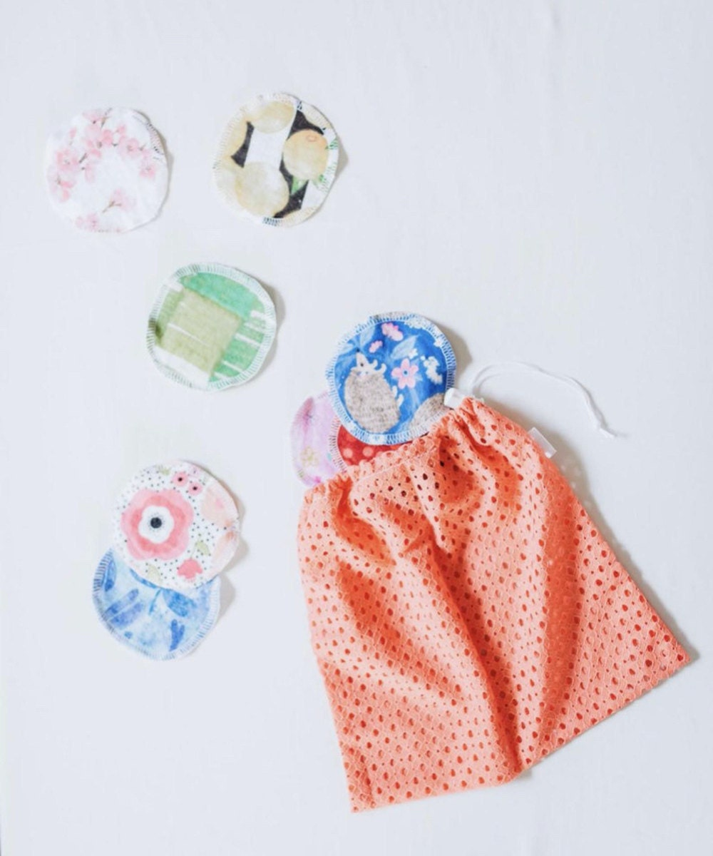 A set of patterned, hand-sewn fleece makeup remover pads pictured spilling out of a fabric bag.