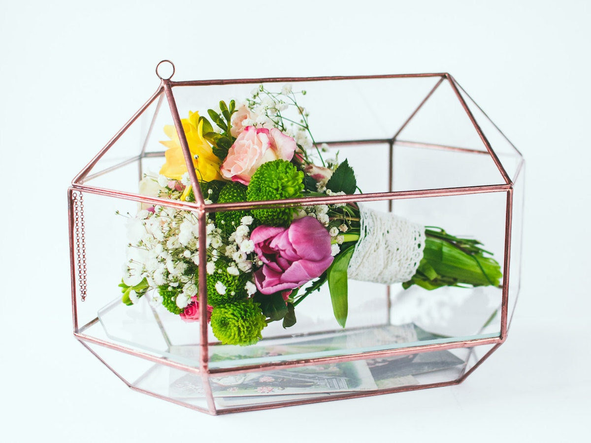 A geometric glass card box and bouquet display case