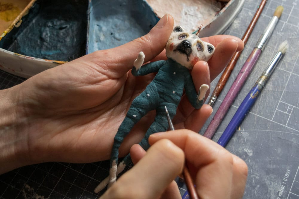 Kayleigh paints the cotton body of a bear ornament