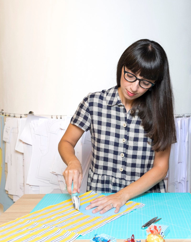 Simona uses a rotary cutter to cut fabric from a pattern in her studio