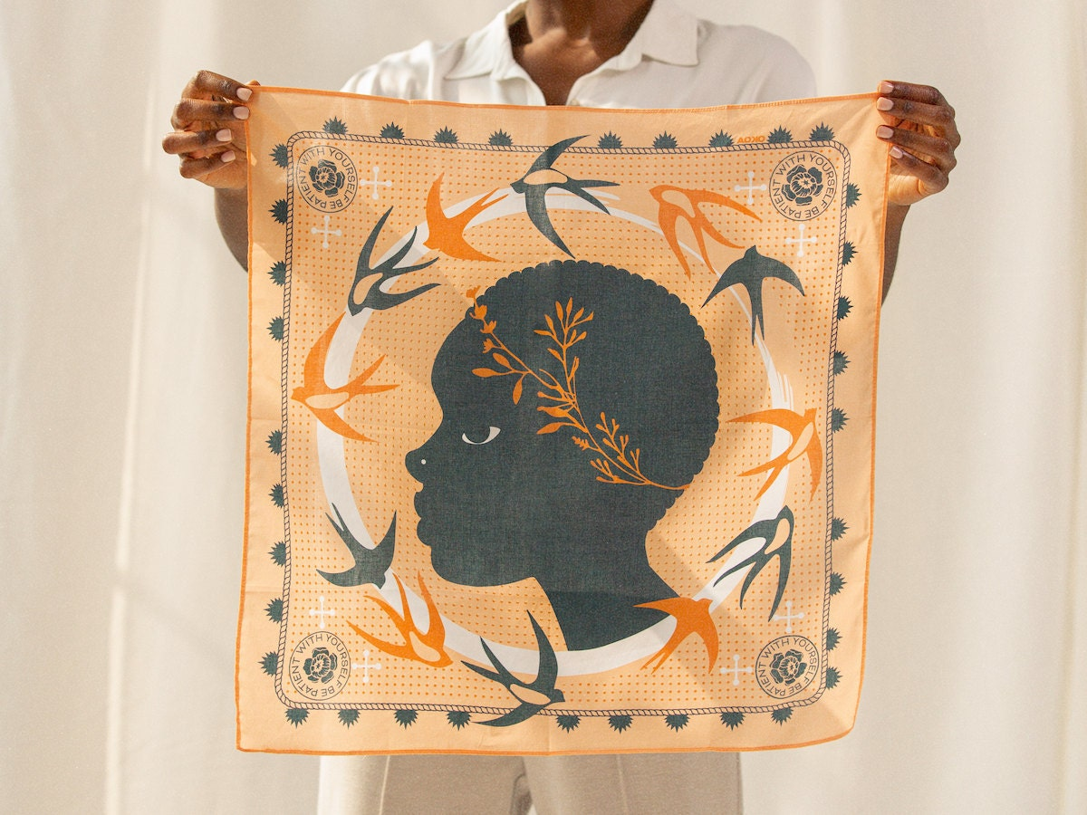 A woman holds up an elegant hand-illustrated scarf from All Very Goods