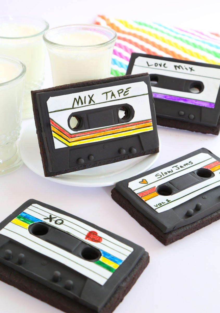 The finished mixed tape cookies on display with cups of milk.
