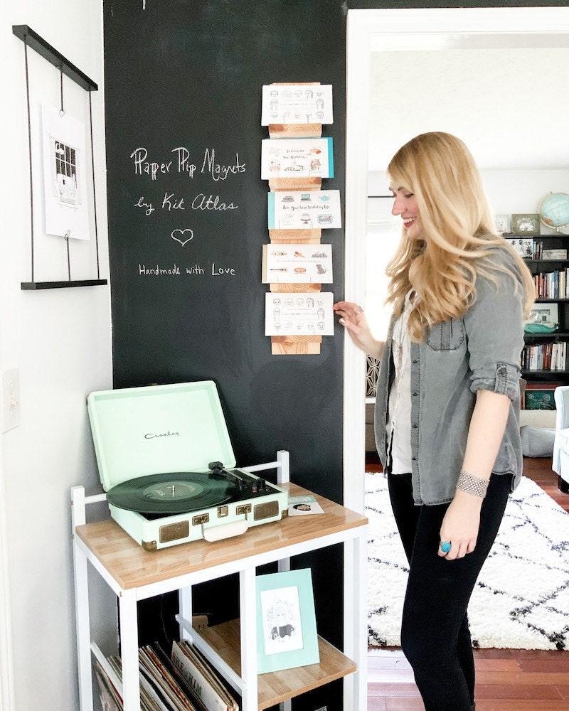 Brittney stands next to a chalkboard wall in her Kit Atlas home studio