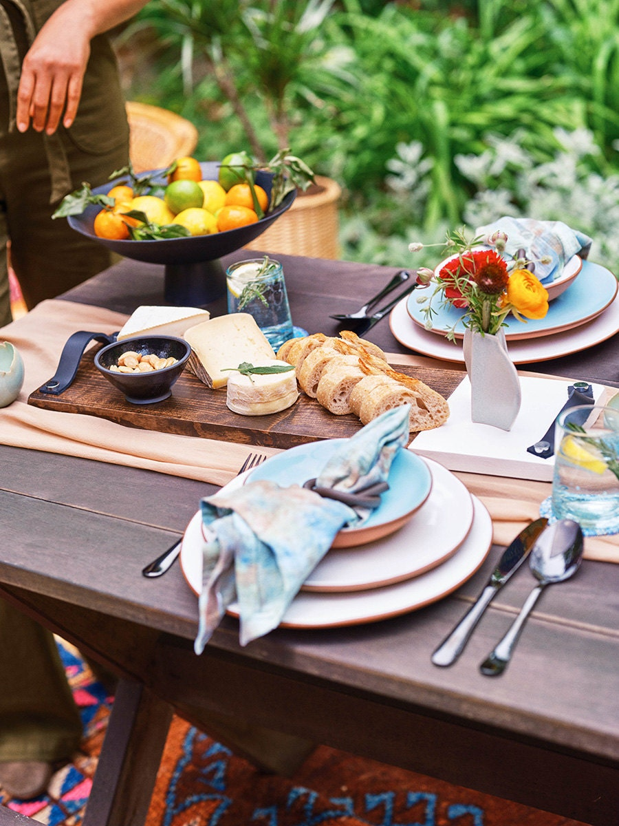 A large cutting board with bread and cheese sits on a decorated outdoor table