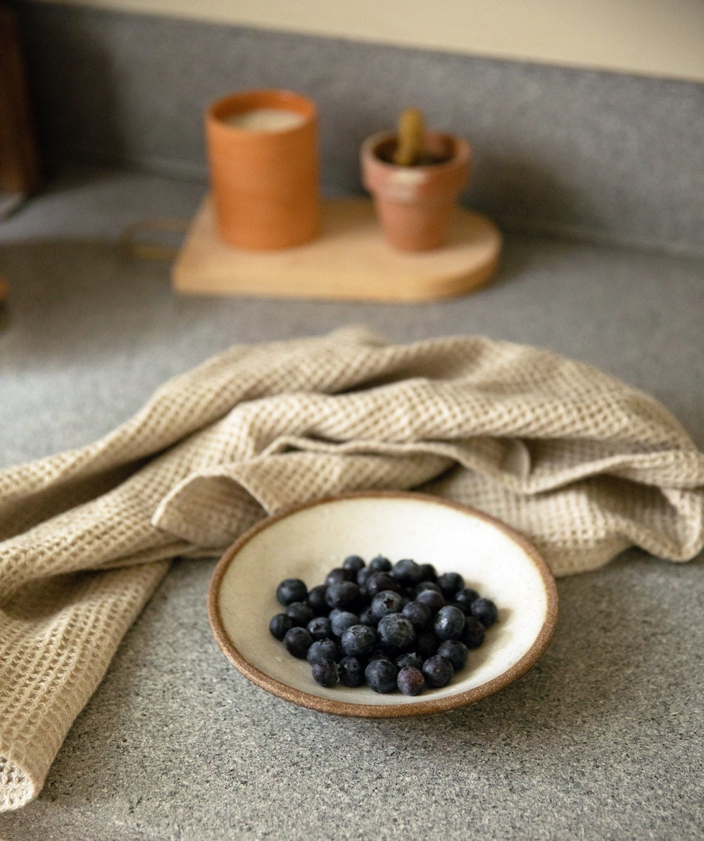 Berries in a bowl arranged on a counter with a tea towel