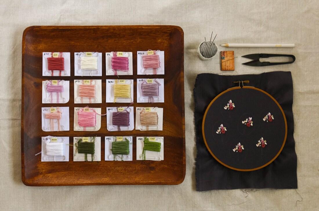 A flat lay of embroidery flosses alongside an in progress hoop