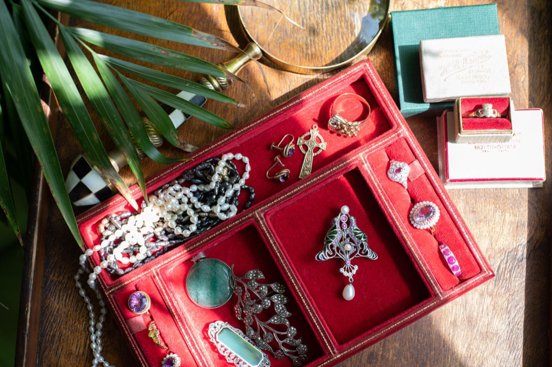 A jewelry tray filled with necklaces, brooches, rings and earrings from KK Vintage Collection