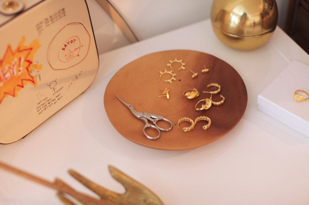 A jewelry dish filled with assorted gold earrings from Omi Woods