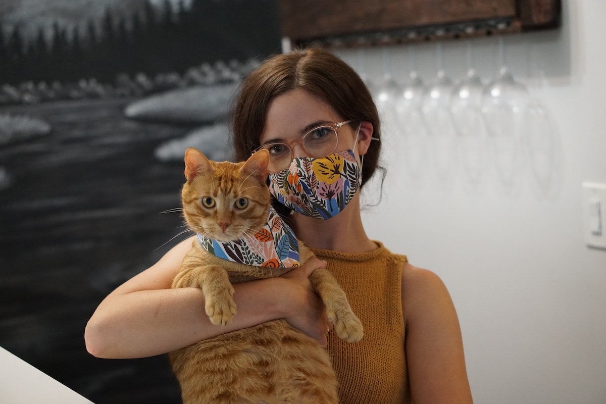 A woman and her cat wear a matching fabric face mask and bandana set.