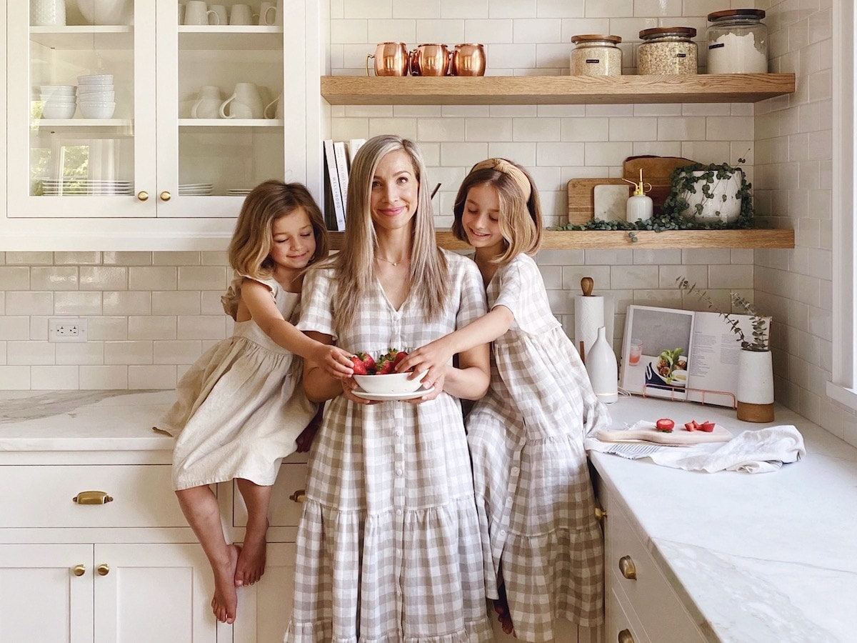 A family photo of Kristine Lee in the kitchen with her daughters, sharing a bowl of strawberries.