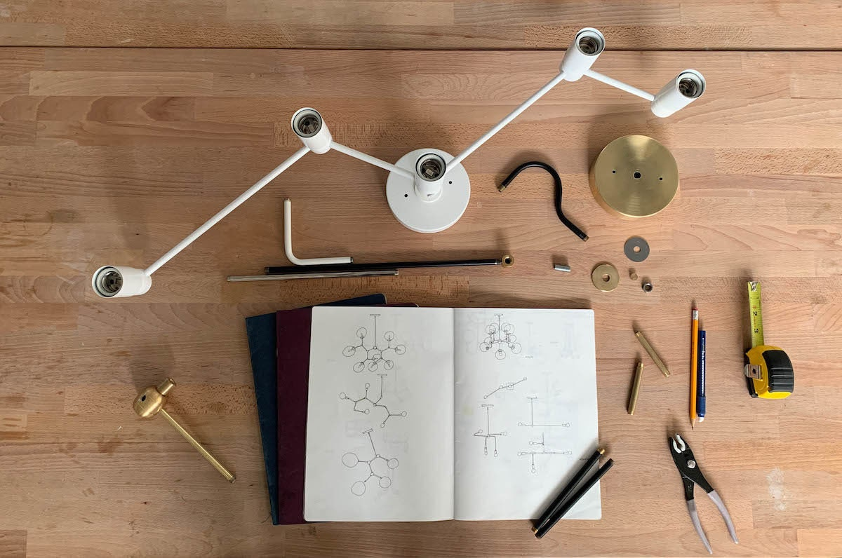 An open sketchbook containing illustrations of various lights sits on a table surrounded by light parts awaiting assembly