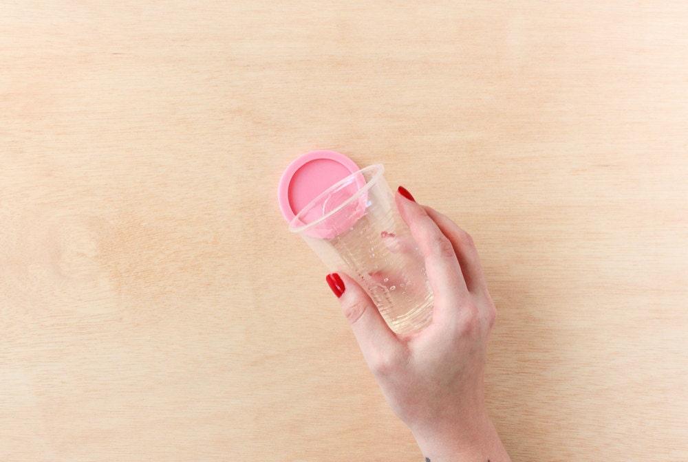 Rachel pours her resin mixture into a circular mold.