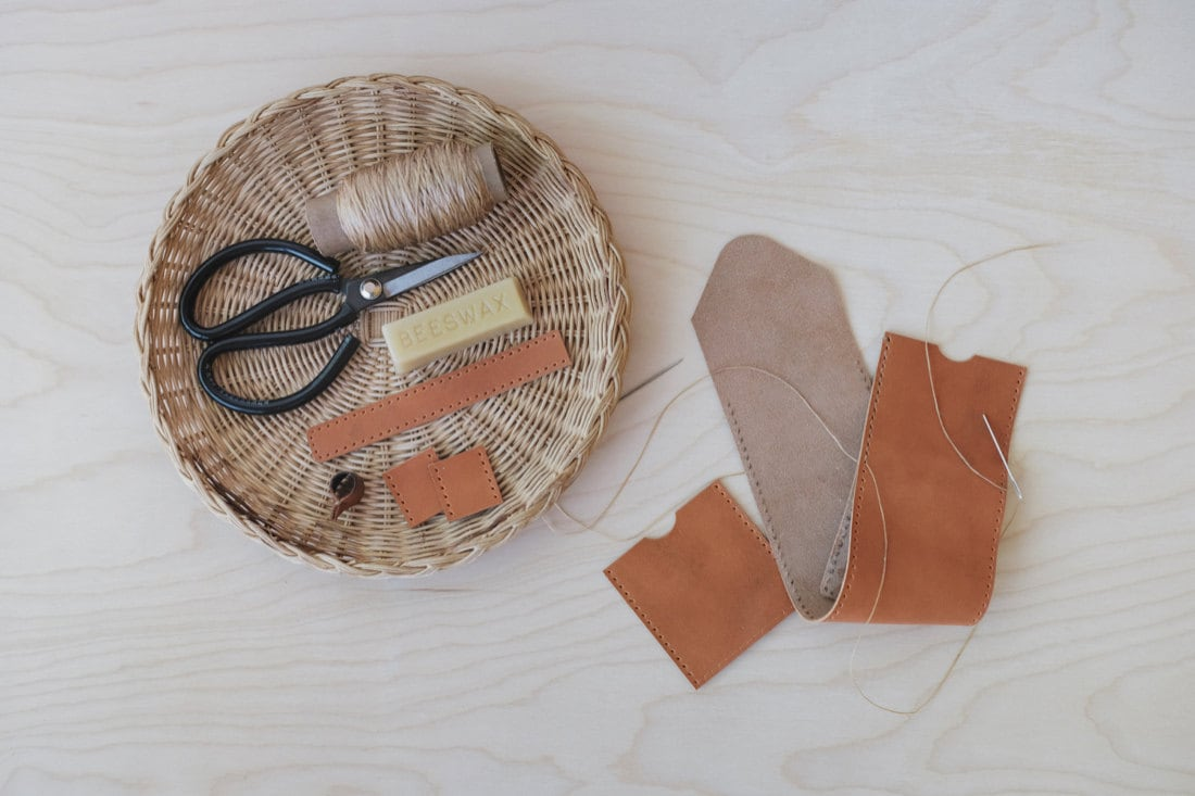 Quynh's materials laid out neatly, including scissors, thread, beeswax, and strips of leather