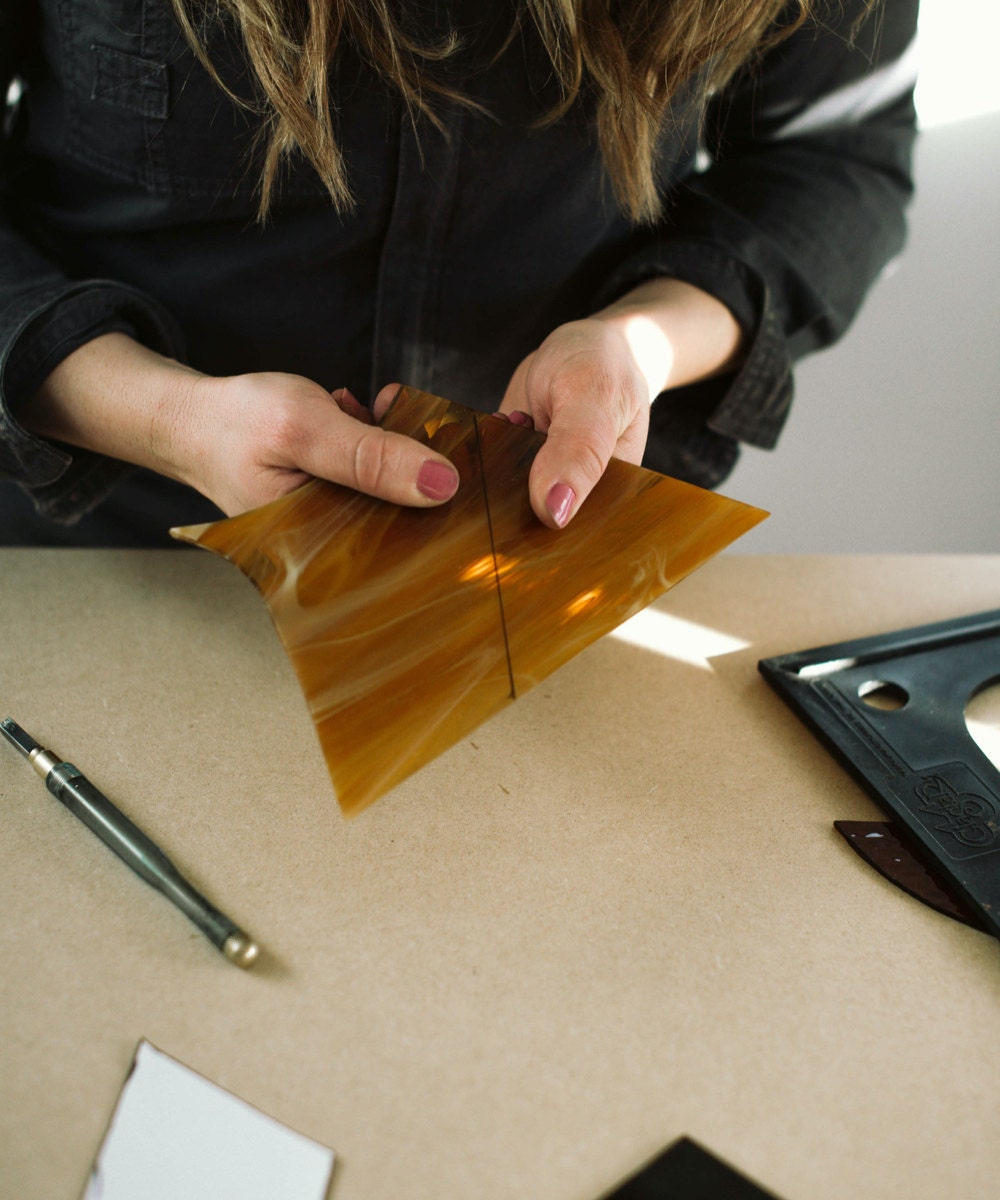 Lauren works on a cut of yellow glass.
