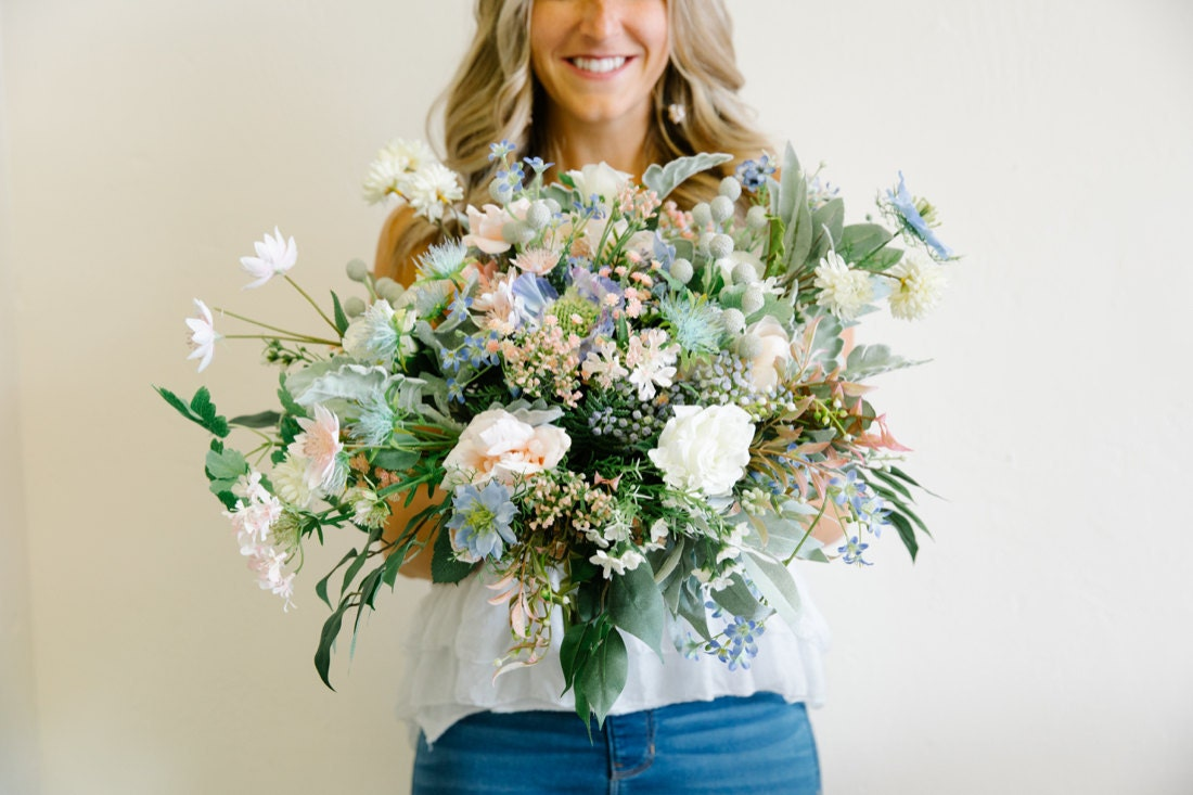 Brittany holds up a finished bouquet