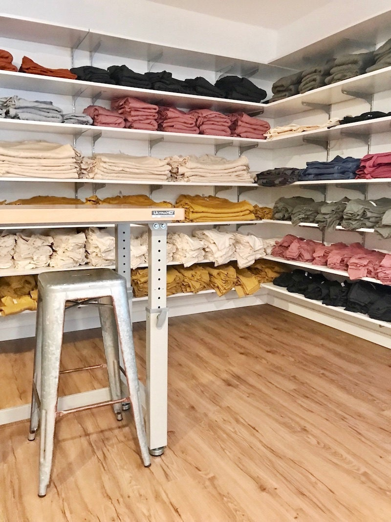 A work table, stool, and shelves of blank totes and T-shirts in Lindsey's studio