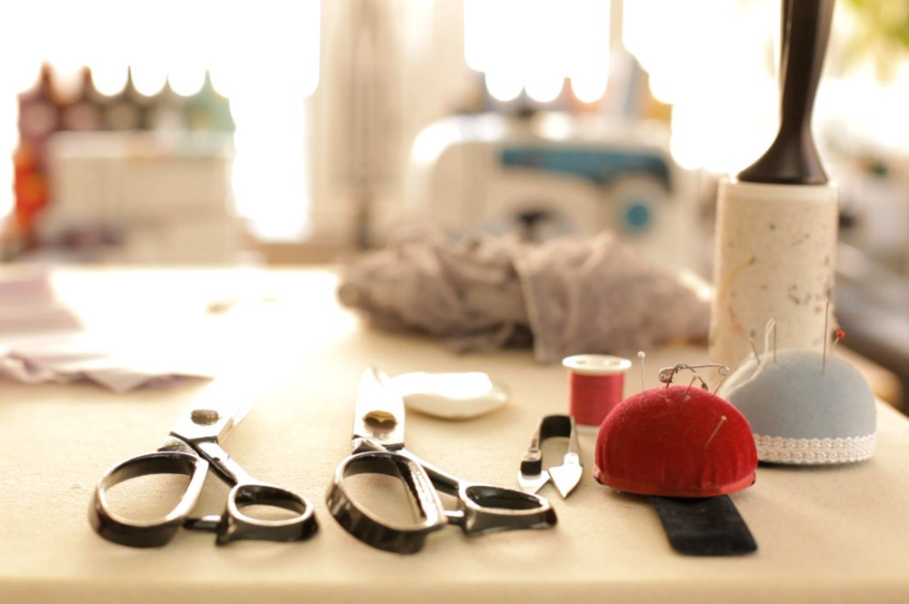 Scissors, pin cushions, thread, and other sewing materials lined up on Elma's workbench