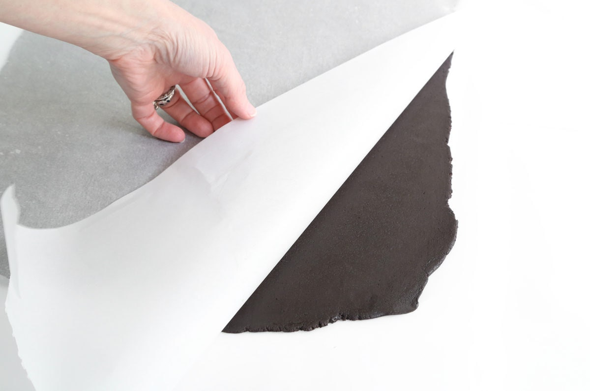 Removing the chilled, flattened dough from the parchment paper.