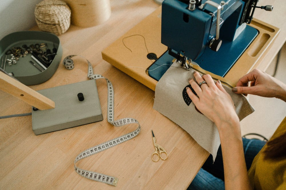 Eda sewing an abstract clutch at her workbench