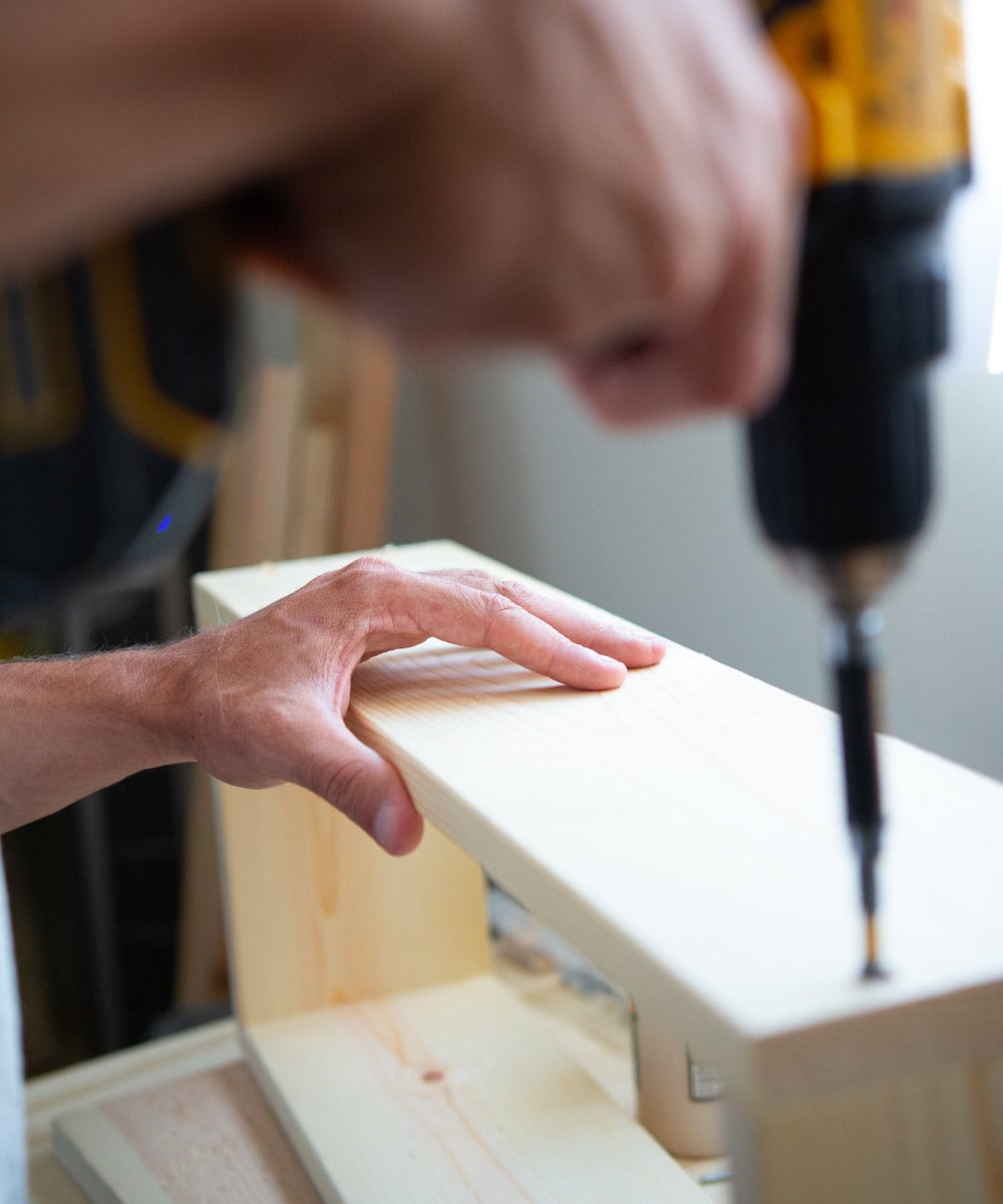Mike drills holes into a floating shelf.