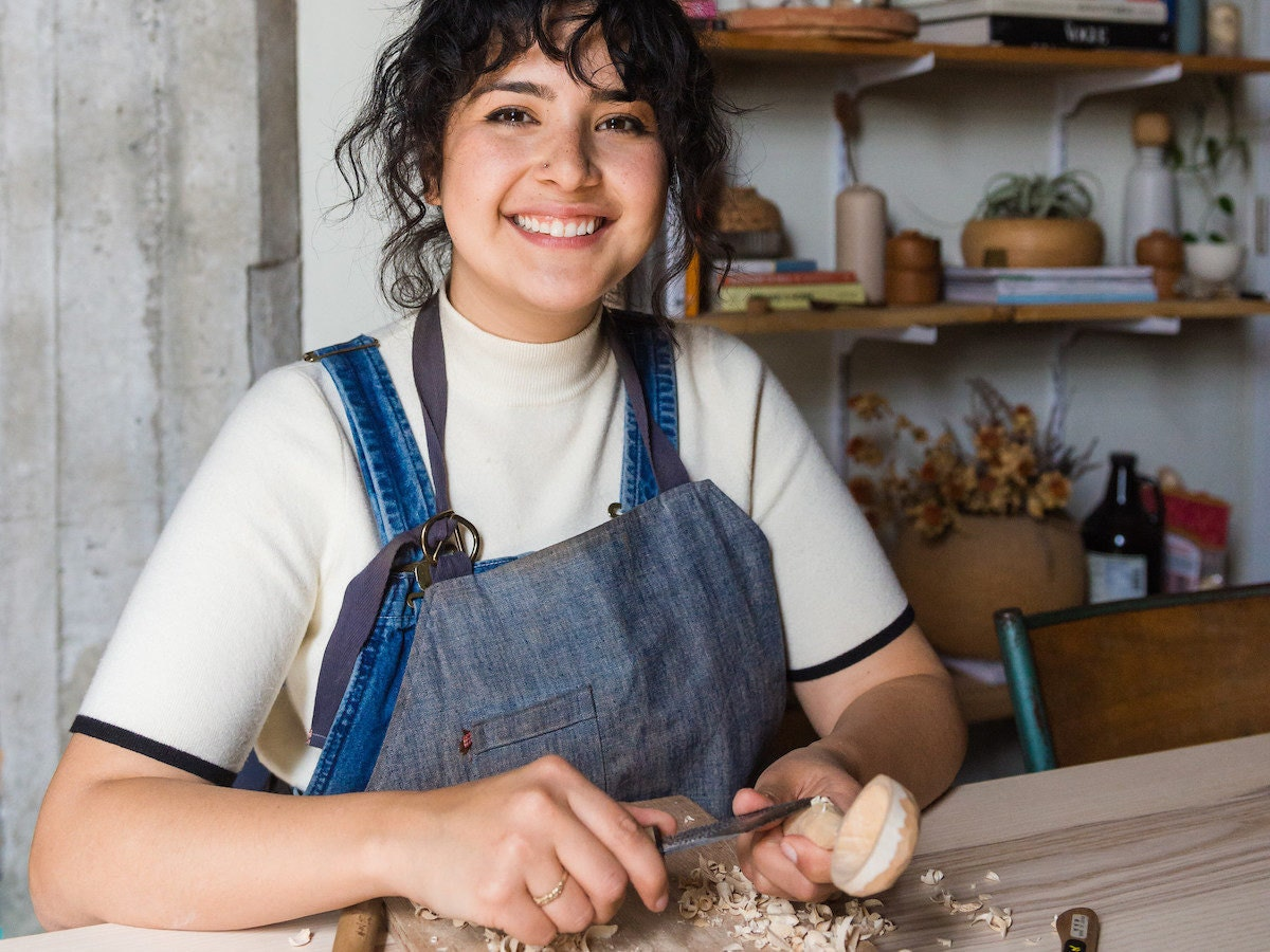 Melanie Abrantes carves a spoon in her sunny Oakland studio