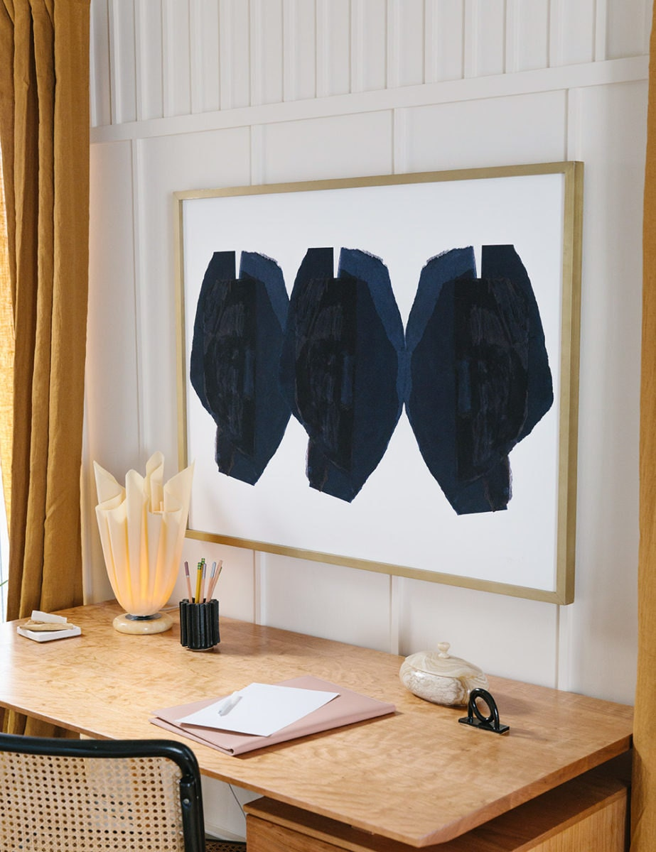 Above the desk is a framed abstract art print with three black circle-like shapes.