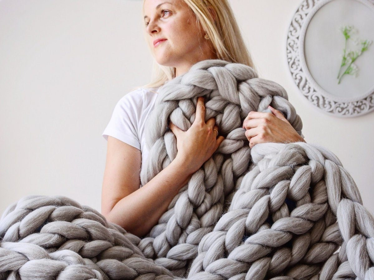 Woman wrapped in a giant chunky knit wool blanket