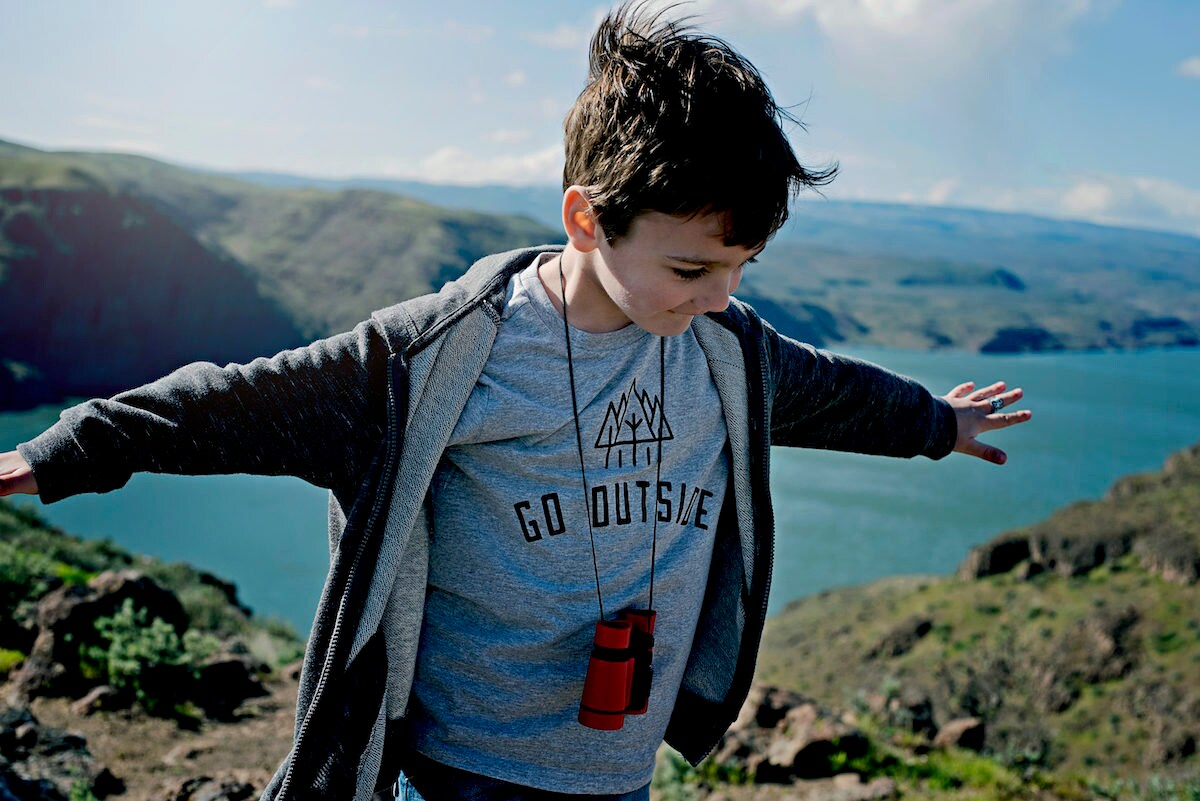 """A boy with binoculars around his neck wearing a """"Go Outside"""" T-shirt on a mountaintop"""